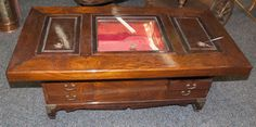 UNUSUAL ORIENTAL WOOD COFFEE TABLE WITH LIDDED COMPARTMENTS ON TOP FOR STORING ITEMS. THE MIDDLE COMPARTMENT IS GLASS AND IS IDEAL FOR DISPLAYING ITEMS. THERE ARE MULTIPLE SMALL DRAWERS AND BRASS ACCENTS. MEASURES 18HX43WX22D. GREAT CONDITION.