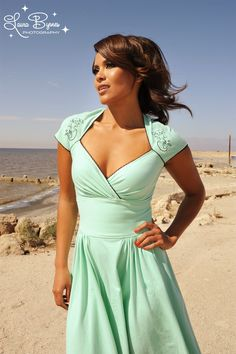 Luscious Dress in Mint with Mira the Mermaid - The Luscious Dress is Pinup Couture's answer to the baby doll dress, but in high-quality stretch cotton knit and a longer length. So comfy, like slipping on your favorite tee, with a flattering, embellished neckline, adorable ric rac trim, and gathers at the skirt. Embroidered at the shoulders with our exclusive design by our own Micheline Pitt, the Luscious will make your day automatically happier!