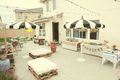 Love the black and white striped umbrellas, little bulb lights strung above the patio, and wood pallet seating!
