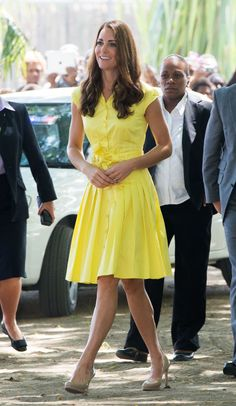 For a casual outing to the village of Honiara on Guadalcanal Island, she looks classic in a bright yellow Jaeger shirtdress and her famous nude L.K. Bennett pumps.