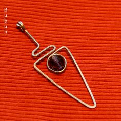 Fialkový oštěp Přívěsek je ručně tepaný se skleněným fialovým korálkem,vyrobený z chirurgickéhoOsteodrátu a proto je vhodný pro alergiky. Přívěsek je vysoký 5 cm.