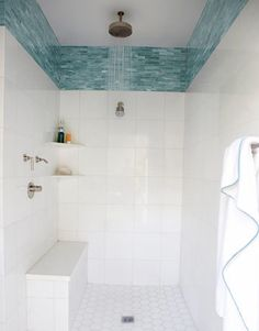 watery blue tile along the top of an otherwise white shower stall