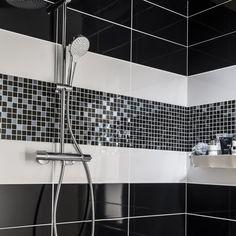 Une douche avec carrelage et mosaïque noir et blanc