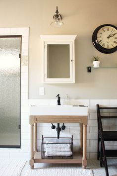 """Sherwin Williams """"mindful grey"""" bathroom with white woodwork, vanities, and oil-rubbed bronze fixtures/clock"""