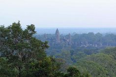 View of Angkor Wat across the jungle, from the nearby hill of Phnom Bekheng (a popular place to watch the sunset)