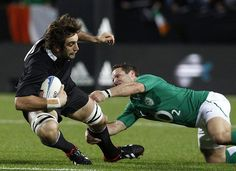 All Blacks humiliate Ireland 60 - 0 on 23 June 2012. Sam Whitelock is tackled by Ireland's Paddy Wallace.