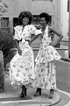 Fashion - Ossie Clark Collection - Radley - 1973  The two creations 'Strictly Confidential' a printed long satin dress worn by Selina, right, and 'Streetwalker', a white printed crepe dress, tie top and layered skirt, worn by Myna Bird, part of the Ossie Clark Collection.
