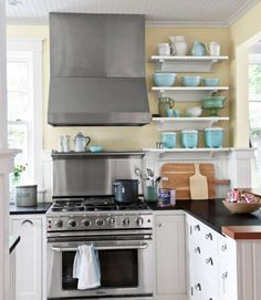 Colors of the Sea  The kitchen's open shelving holds a collection of vintage bowls, pitchers, and canisters in shades of blue, green, and white.