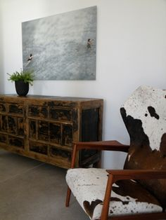 Distressed dresser + cowhide + armchair + oversize bw print