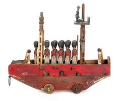 """Realized Price: $ 1185    German carved wooden pull toy of a ship on wheels with soldiers and cannons, retaining a polychrome decorated surface, 8"""" h., 9"""" l. Provenance: John and Madeline Nies."""