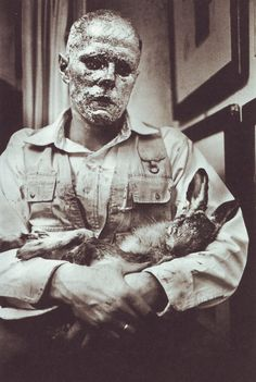 How To Explain Pictures To A Dead Hare - a performance enacted by Joseph Beuys on 26 November 1965. With his head entirely coated in honey and gold leaf, he explained pictures to a dead hare. Whispering to the dead animal on his arm in an apparent dialogue, he processed through the exhibit from artwork to artwork. Public could only watch from outside through the windows of the gallery.