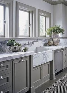 Grey cabinets and marble farmhouse sink.
