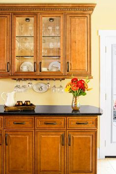 Devise a kitchen bar by swapping wood panels in two upper cabinets for glass. Then add an undercabinet stemware holder. | Photo: Deborah Whitlaw Llewellyn | thisoldhouse.com