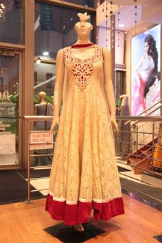 cream and maroon combination net fabric anarkali style suit with contrast gold embroidery on the front finished with maroon thread boundaries.