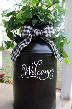 Look what you can do with an old milk can, ribbon, ivy, and vinyl lettering.... Adorable! I'm going to put this on my front porch...
