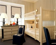 daniel romualdez for tory burch classic kids' bedroom--black and white striped wallpaper, roman shades, skirted parsons chairs, greek key fretwork trim, bunk beds