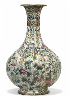 A CHINESE CLOISONNÉ ENAMEL LOBED BOTTLE VASE 19TH CENTURY Decorated with butterflies amongst flowering branches on the six-lobed body, and densely scrolling lotus on the fluted slender flaring neck, all reserved on a white ground