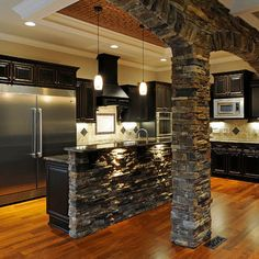 Stone decor, black cabinetry, stainless steel appiances.