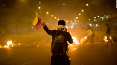 A Venezuelan protester waves a flag in front of a burning barricade in Caracas on Friday