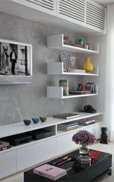 Objetos fáceis de achar: gavetões, mantêm em ordem a coleção de DVDs. Sem puxadores, não pesam no visual da estante. A parede, onde foi instalada a TV, recebeu uma pintura especial (Cada Canto), imitando cimento queimado. Projeto de Carla Basiches.