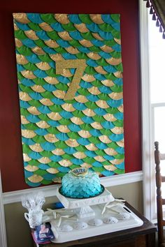 Fish scale backdrop made with gold, blue and green cupcake liners + gold glitter paper number {Stephanie Howell}