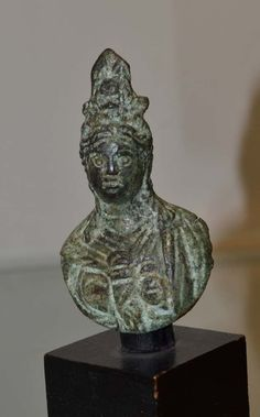 """Bust of Isis Fortuna, wearing a Hellenistic robe, and has a combination of remains of cow horns, sun-disk, and ears of corn as a crown on her head. Probably used as a steelyard weight. 2nd/3rd Century. 2 3/8"""" high. Mounted. From a Connecticut private collection, acquired 1976 from the Jerusalem art market."""