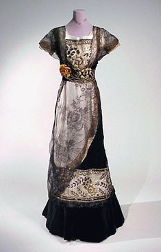 Circa 1910 black velvet and lace evening gown, Washington, D.C. With slightly raised waist emphasized with wide band, short net sleeves, square neckline, A-line skirt with small train, the bodice sides and part of skirt overlaid with fine black lace, the center bodice, waist, and lower part of skirt further decorated with floral embroidered tulle worked in gold metallic. Black and white silks and beads, the lower edge of skirt band trimmed with black fur.