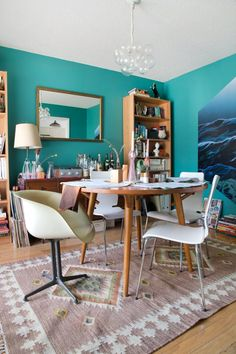 Simple dining room: round table, 2 bookshelves, sideboard, mirror, patterned rug