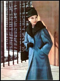 Model in blue mohair coat with black astrakhan collar and worn with astrakhan cap, by Jacques Heim, photo by Pottier, 1959