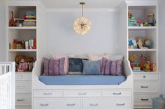 Amazing boy's nursery design with pale blue paint color and crisp white moldings. Art deco crystal pendant over white daybed with blue cushions and blue and pink pillows. White storage daybed flanked by vertical built-in cabinets filled with books and toys.