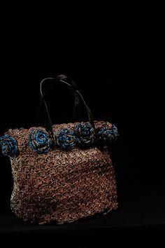 """""""A nos actes manqués""""  Sac à main en raphia crocheté  Fleurs de couleur en raphia en bordure du sac  Intérieur doublé en tissu  Anses en cuir  Dimensions : 40x30x25"""