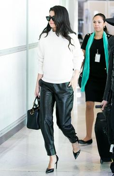 Selena Gomez wears a ribbed white sweater, leather pants, pointed-toe pumps, black sunglasses, and a satchel