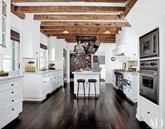 White kitchens will never go out of style. In a modern home, a cool hue makes a clean statement with lacquered white cabinets and stainless-steel fixtures. For the traditionalist, rustic wood ceiling beams, walnut floors, or copper pots hung from a ceiling rack can warm up  alabaster walls. Whatever your preference, these 30 examples from the Architectural Digest archive prove the enduring versatility of the classic color in kitchen design.    At his home in Amagansett, New York, talent…