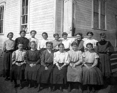 A group of middle-school-aged girls in front of their country schoolhouse in Downsville, Wisconsin in 1905. They continue to wear the standard skirt and blouse ensemble that originated in the mid-1890s. SEE the younger girls peaking out from the window and behind the door.