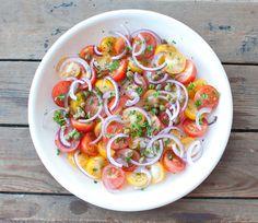 Tomatensalade met rode ui en kappertjes; een salade voor op warme dagen. Serveer de tomatensalade bij de barbecue, als lunch of bij een mooi stuk vlees.