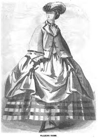 """March 1861 Peterson's Magazine; The Highland walking dress of plain delaine and held up with """"pages"""" over a Balmoral skirt usually made of gray flannel &  trimmed with red horizontal stripes.  A loose jacket is worn over a linen chemisette. The jacket is trimmed in braid &  buttons, an embassy hat with plume adorns the head."""