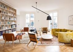 For this Paris living room, designer Charlotte Macaux Perelman combined Scandinavian armchairs with a ceiling light by the Bouroullec Brothers and bookshelves by Martin Szekely. See more of Perelman's work in #Introspective.