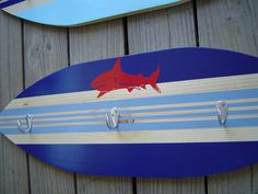 27 inch SHARK SURFBOARD HoOK RaCK for towels clothes keys .  Red Blue Hawaiian Surf Wall Decor.   Custom Painted. 150 Designs and 3 sizes. wow. $129.99, via Etsy.  @amy nelms