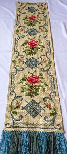 Lovely vintage handmade tapestry / table runner with Roses. Amazing handicraft cross stitch on linen canvas there is a lining at the back very precise work In an excellent vintage condition fringes in 3 colors Approximate measurements: 15 x 62,2 (38 cm x 158 cm) - with fringe the length is