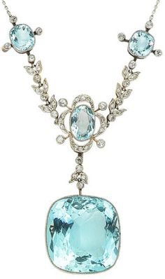 An early 20th century aquamarine and diamond necklace. The front composed of three delicate quatrefoil clusters, millegrain-set throughout with cushion-shaped and oval-cut aquamarines and old brilliant and single-cut diamonds, connected by similarly set single-cut diamond foliate swags, suspending a large cushion-shaped aquamarine pendant, mounted in platinum and yellow gold, on a fine trace-link chain. Via Bonhams.