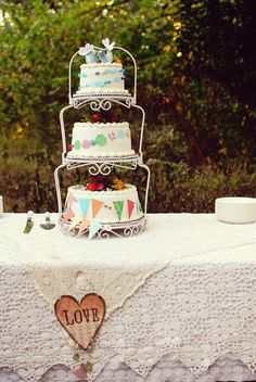 three-tiered, bunting-bedecked cake - less expensive than stacked cakes