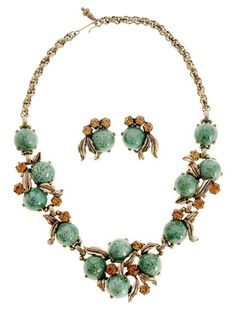 Talk about vintageous! This bold vintage signed Schiaparelli necklace is green glass that looks like Jadite, as cabochons in a gold tone leaf setting. There are amber colored rhinestones in among the