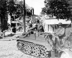 """Trois soldats américains observent le paysage dévasté de Carentan après les combats Ils ont """"emprunté"""" une moto chenillée, NSU """"Kettenrad"""" type HK 101SdKfz 2 + remorque, allemande dont les régiments paras étaient largement dotés. Le para en HBT fait le plein des jerrycans à eau La censure a masqué tous les patchs d'épaule et de casque, mais la photo référencée par le Signal Corps N°190625 permet de savoir qu'il s'agit de paras US du 502nd Parachute Infantry Regt de la 101st Airborne Div."""