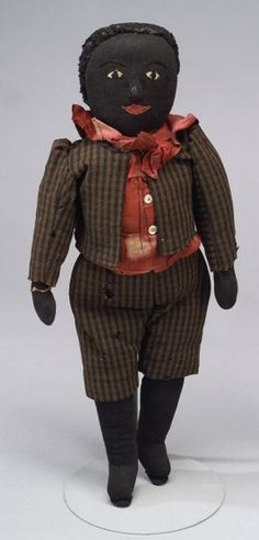 Handmade Black Boy Rag Doll, late 19th/early 20th century, black stockinette with embroidered features and needle-sculpted and padded nose, pink-red smiling mouth (circular run by left eye, wear on nose), stitched-on black wooly wig, mitt hands, stitched joints at shoulders and hips, brown and black striped wool suit (some moth damage), burgundy cotton shirt with ruffled collar and bow (spotty fading), ht. 20 in.