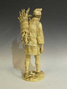 A large Japanese ivory figure, modelled as a man holding chrysanthemum blooms and carrying kindling in basket to his back, engraved detail, 39cm high, the base with red lacquer seal bearing signature, Meiji period