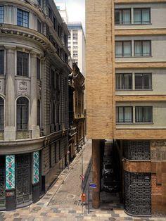 O contraste entre edifícios antigos e novos numa rua estreita do Centro da Cidade do Rio de Janeiro, Brasil.