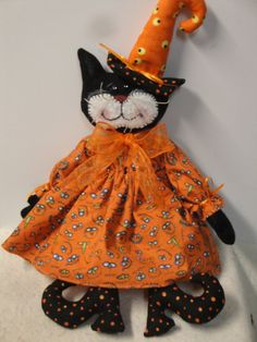 An adorable little Halloween Witch black cat with her fun Halloween dress. She measures 18 inches tall from her feet to the top of her witches hat. She is made from black flannel fabric for the body and her face. The face has a white wool felt insert. She has black beads for her eyes, sisal for her whiskers. The face is been painted to show her facial features. She wears a fun Halloween themed dress in orange with different fun eyes in the fabric. A wear of bloomers made from a tan colored…