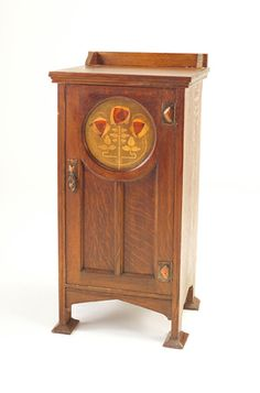 English Arts & Crafts cabinet with medallion of Glasgow roses inlaid in contrasting woods – September 2004 Sale Price: $2,115 – Rago Arts and Auction Center