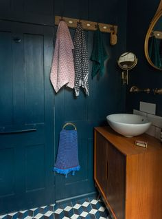 The encaustic floor tiles from Mosaic del Sur were the most expensive part of the bathroom refit (and a perfect color match for the Hague Blue on the walls).  The vanity unit is a vintage record cabinet they added hairpin legs to. The towels are from H&M.