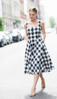 A graphic, gingham dress is worn with minimal nude mules and a dainty necklace